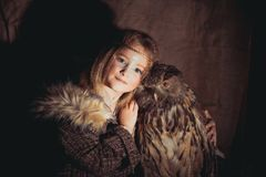 Girl in the style of boho with an owl. Boho chic hugs big owl royalty free stock photo