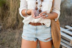 A hippie girl in ornaments boho chic keeps a shell of snails in her hands Stock Images