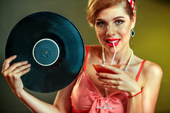 Girl in style keeps vinyl record and drink martini cocktail . Royalty Free Stock Photography