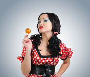 Girl in the style of pin up licking a candy Royalty Free Stock Photos