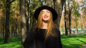 Girl in stylish coat and hat with wide brim outdoors. Attractive young girl in stylish coat and hat with wide brim looking at the camera and smiling outdoors in royalty free stock photo