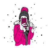 A girl in a stylish down jacket and a beautiful hat with a fluffy bubo. A woman is holding a smartphone and making selfies. Royalty Free Stock Photo