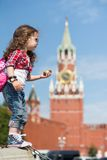 Girl in stylish dress and sunglasses near the Kremlin. The little girl in stylish dress and sunglasses near the Kremlin with a compass in hand stands in profile royalty free stock image
