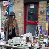 The girl in a stylish hat sells vintage glass bottles on Brick Lane Royalty Free Stock Image