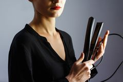 Girl stylist holding a Curling iron for hair. royalty free stock photography