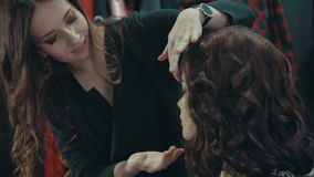 A girl stylist talking of evening make-up in the boutique of women`s clothing. stock video footage