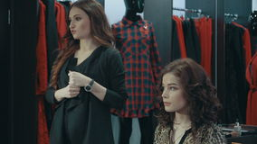 A girl stylist talking of evening make-up in the boutique of women`s clothing. A young stylist talks about the basics of creating a harmonious image for stock video footage