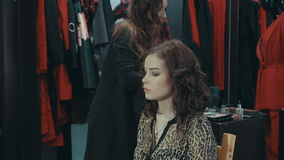 A girl stylist talking of evening make-up in the boutique of women`s clothing. stock video