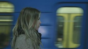 Girl in the Subway Waiting For Train. The girl with long hair standing in the subway and looking at the camera. Behind her passing train stock video footage