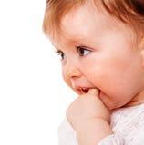 Girl sucking finger. Close up Portrait of baby girl sucking finger isolated on white background Royalty Free Stock Image