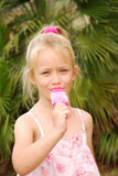 Girl sucking ice lolly. A cute little girl with happy smiling face sucking and enjoying an ice lolly Royalty Free Stock Images