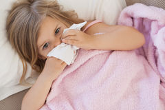Girl suffering from cold as she lies in bed Royalty Free Stock Images