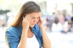 Girl suffering migraine in the street. Painful girl suffering migraine touching temple in the street Royalty Free Stock Image