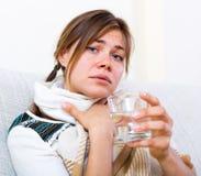 Girl suffering of sore throat. Sad young girl suffering of sore throat and fever at home Royalty Free Stock Photos