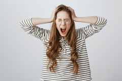 Girl suffers from depression, being under pressure from deadlines and work. Mad cute woman in glasses, screaming or. Shouting with hands on head, having stock photography