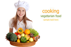 The girl in a suit of the cook with a basket of vegetables and fruits on isolated background Royalty Free Stock Image