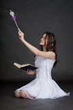 Girl in suit of the fairy with magic wand on black Stock Photos