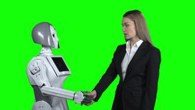 Girl welcomes the robot takes his hand and says hello. Green screen. Girl in a suit greets the robot, takes his hand and says hello. Green screen