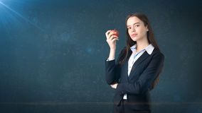 Girl in suit holds bright vibrant apple in hand, symbolising new ideas and fresh concepts or healthy lifestyle in office Stock Photo