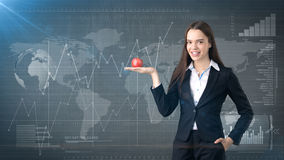 Girl in suit holds bright vibrant apple in hand, symbolising new ideas and fresh concepts or healthy lifestyle in office Stock Photography