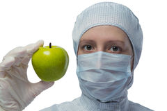 Girl in a suit laboratory shows green apple. Beautiful woman dressed as a medical shows a green apple in hand Stock Photo