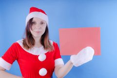 Girl in a suit `Santa Claus` with a sign on a blue background. The concept of discounts and sales for Christmas. Discount on holid royalty free stock photos