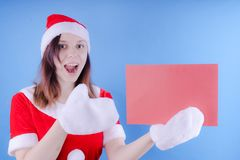 Girl in a suit `Santa Claus` with a sign on a blue background. The concept of discounts and sales for Christmas. Discount on holid stock image