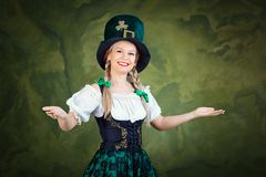 The girl in the suit of St. Patrick is welcome on a green backgr. Ound. St. Patrick`s Day Royalty Free Stock Photo