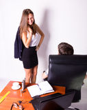 Girl in a suit stands next to a desk. Sexual harassment in the workplace. Stock Photos