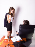 Girl in a suit stands next to a desk. Sexual harassment in the workplace. Stock Photo