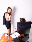 Girl in a suit stands next to a desk.  Sexual harassment in the workplace. Royalty Free Stock Image
