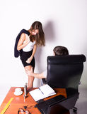 Girl in a suit stands next to a desk. Sexual harassment in the workplace. Stock Photography