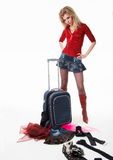 The girl with a suitcase. The girl looks at scattered things from a suitcase Royalty Free Stock Photo