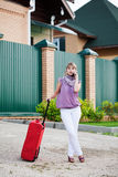 Girl with a suitcase. Calls a taxi by a mobile phone Royalty Free Stock Image