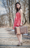 Girl with suitcase. Stops the car on road Stock Photography