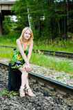 Girl with a suitcase. Tired girl sitting on a suitcase Royalty Free Stock Image