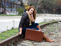 Girl on a suitcase along the train tracks Stock Image