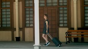 Girl with suitcase arrived to old cinematic train station at holiday travel. Girl with luggage suitcase arrived to old cinematic train station during summer stock video footage