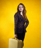 Girl with a suitcase on background of yellow wall Royalty Free Stock Images
