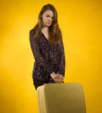 Girl with a suitcase on background of yellow wall Royalty Free Stock Photography