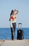 Girl with suitcase on the beach Stock Image