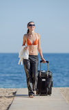 Girl with suitcase on the beach Royalty Free Stock Image