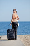 Girl with suitcase on the beach. Royalty Free Stock Photo