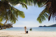Girl with a suitcase on the beach Stock Photography