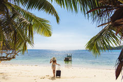 Girl with a suitcase on the beach Royalty Free Stock Photography