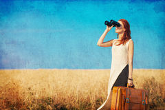 Girl with suitcase and binocular at countryside road Stock Photo