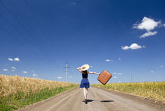 Girl with suitcase at country road.