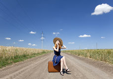 Girl with suitcase at country road. Stock Photos