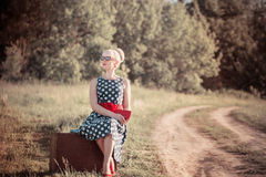 Girl with suitcase at countryside Stock Image