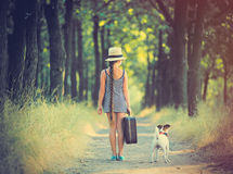 Girl with suitcase and dog Stock Image